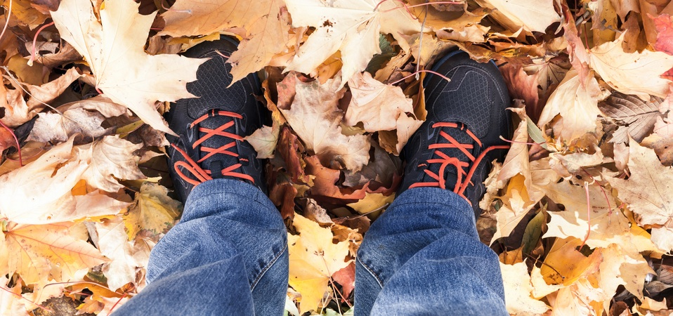 Male feet standing on yellow maple leaves